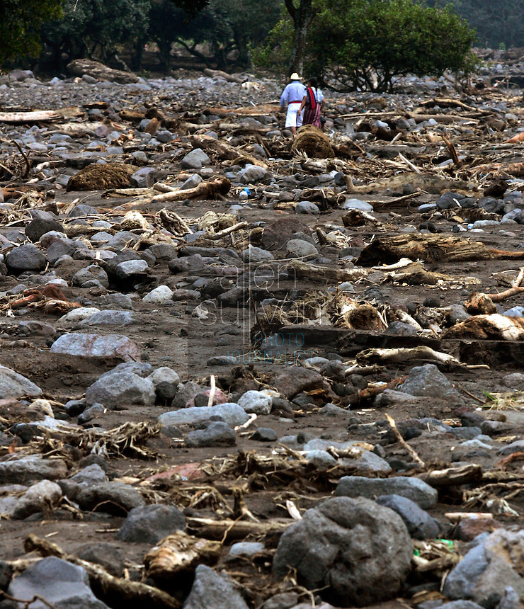 A Mayan couple picks its way through an area that mudslides destroyed earlier in the month when Hurricane Stan spawned torrential rains over parts of Central America. Hundreds of people and houses were buried in the mudslide that caught the area of Lake Atitl&aacute;n by surprise in the early morning hours.<br />