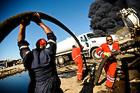 PDVSA contractors work to clean up oil waste outside of the Amuay refinery in Punto Fijo, Venezuela on Sunday.  Pools of oil filled the streets, apparently seeping from underground pipes burst by the explosion at the refinery early Saturday morning, killing at least 39 people.