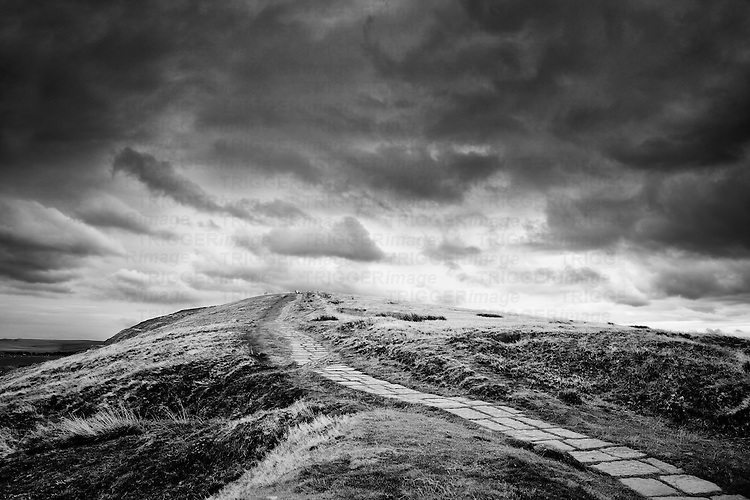 Stone path winds through Peak District moorland featuring rock formations on the horizon and large brooding sky