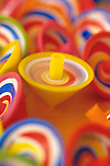 One yellow spinning top amongst a bunch of multi-colored motionless spinning tops,