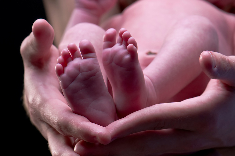 Close up of newborn feet and adult hands, conceptual shot of parenthood caring.