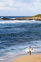A surfer looks out at the ocean at Ho'okipa Beach on Maui.
