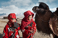 Two young Kyrgyz girls fetching water with a Bactrian camel..Ech Keli, Er Ali Boi's camp, one of the richest Kyrgyz in the Little Pamir..Trekking with yak caravan through the Little Pamir where the Afghan Kyrgyz community live all year, on the borders of China, Tajikistan and Pakistan.