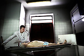 Sochaczew 07.11.2006 Poland<br /> Autopsy room in Sochaczew hospital. on picture /one of the best thanatopraxis in Poland Adam Ragiel..In Poland there are about 20 people who prepare corpses for funerals, but all of them are associated with undertakers. Adam Ragiel works alone, he is a true freelancer, the only professional who specializes in all aspects of thanatopractice. He complains that there are too many cases of corpses being prepared in an unacceptable way. I'm often called up to correct the job. His skills are recognized not only in Poland. He is known in Germany, Italy, Great Britain, but mainly in America.They respect me and trust my work, because I never disappointed them, unlike some other specialists', he admits with a smile. This young man of 26 found in his travels his true passion and vocation. Everywhere he goes he is well respected and trusted. In every place he visits people thank him and express their joy. That applies to the family of the deceased as well as the undertakers who hire him, in America and amost all over Europe. It is an amazing success achieved by his own sacrifice and dedication.I do it for all those who want to see their loved one for the last time.If they were unable to do it, they would suffer even more. That's why I put my whole heaheart into it; in order to soften the pain they must feel as they stand in the chapel to say their last good-bye. You don't know how important it is to them and to me<br /> ( &copy; Adam Lach / Napo Images)