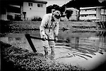 "83 year old farmer slowly reinforces walls of rice paddy what in his lifetime has become a farm swallowed by the capital's western suburbs, where  the average age of farmers hovers around 60 years, Naganuma, Tokyo, Japan.  When asked whether his son continues farming, he responded that his son has a ""money job"".   Financial incentives have steadily drawn the younger generations of Japanese away from the rural life."