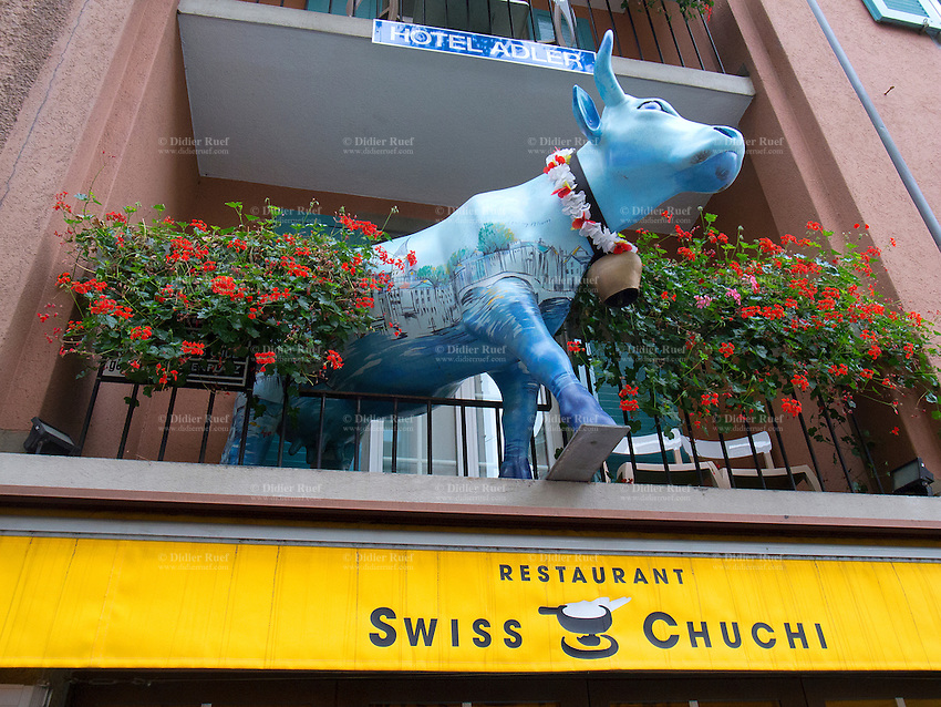 Switzerland. Canton Zürich. Zuerich. Old town. Niederdorf area. A blue cow on a balcony with flowers and a restaurant selling swiss cheese foundue. Hotel Adler. Hotel sign in exterior of building.Fondue is a swiss dish of melted cheese served in a communal pot (caquelon) over a portable stove (réchaud), and eaten by dipping long-stemmed forks with bread into the cheese. 7.11.12  © 2012 Didier Ruef