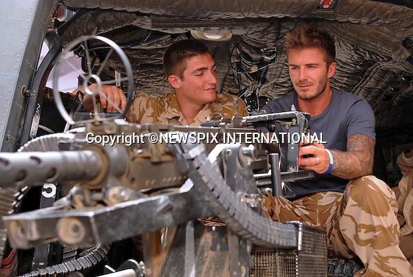 """DAVID BECKHAM.being shown the mounted Heavy Machine Gun on an Army Lynx helicopter by Lance Corporal Chandler, 9 Army Air Corps..David Beckham paid a surprise goodwill visit to UK and US troops in Camp Bastion. He met with hundreds of soldiers and gave away signed England shirts and memorabilia. He was, he said, 'overwhelmed' by the stories of courage he heard..Beckham arrived on Friday night on a Royal Air Force C17 aircraft, stepping off into 45 degree heat in body armour and helmet..After a night's sleep, he ate breakfast in the cookhouse, moving from table to table signing autographs and having photographs taken_Camp Bastion, Helmand Province, Afghanistan_22/05/2010.Photo Credit: ©LLoyd_Newspix International..**ALL FEES PAYABLE TO: """"NEWSPIX INTERNATIONAL""""**..PHOTO CREDIT MANDATORY!!: NEWSPIX INTERNATIONAL..IMMEDIATE CONFIRMATION OF USAGE REQUIRED:.Newspix International, 31 Chinnery Hill, Bishop's Stortford, ENGLAND CM23 3PS.Tel:+441279 324672  ; Fax: +441279656877.Mobile:  0777568 1153.e-mail: info@newspixinternational.co.uk"""