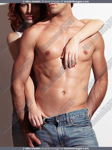 Sexy couple photo of a young woman standing behind a man with muscular bare torso. Isolated on white background.