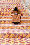 A hooded man sits on colorful steps, Essaouira, Morocco