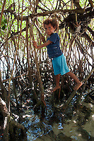 Raja Ampat Archipelago, West Papua, Indonesia, December 2010. Children play in the blue water Mangroves near Yembeser village. Thousands of small islands fringed by coral reefs and blue water mangroves litter the Raja Ampat archipelago. The turquoise and blue waters are teeming with marine life that forms the livelihood for the local Papuan population. The Raja Ampat Research & Conservation Centre (RARCC) supports the locals to develop a community based, sustainable tourism project, inviting visitors to explore their islands by sea kayak and experience the culture by staying amongst the local people in traditional style homestays. Photo by Frits Meyst/Adventure4ever.com