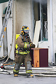 fireman outside smoking  building wearing full protective gear
