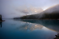 Mist rising from Moraine Lake, with Wenkchemma glacier shrouded in fog and mist. Reflection over Moraine Lake