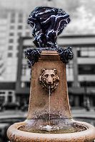 Water flows from the mouth of a carved figure in the Latham Fountain in Latham Square, downtown Oakland, California.