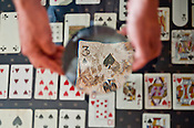 """Tom Whiteside, owner of Durham Cinematheque, holds a magnifying glass over the first card he found: 3 of spades for his installation; """"Cards: Two Decks"""" on Thursday June 28th 2012."""