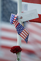 A flower is attached to the pole of one flag in a field of 3,000 flags installed in a wheat field in Maria Stein, Ohio, Monday, September 11, 2006. The display was erected to honor military, police, fire fighters, and emergency workers on the anniversary of the attacks on the World Trade Center and Pentagon in 2001.<br />