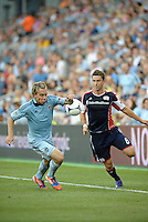 Seth Sinovic (16) defender Sporting KC and Chris Tierney (8) midfield New England Revolution fight for the ball..Sporting Kansas City and New England Revolution played to a 0-0 tie at LIVESTRONG Sporting Park, Kansas City, KS.