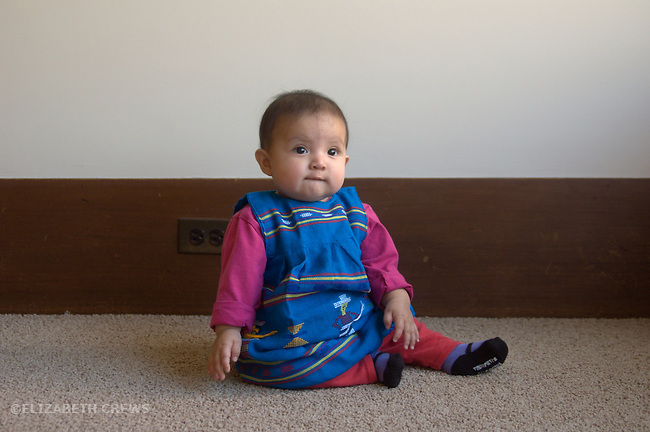 Berkeley CA Contemplative eight-month-old Guatemalan girl sitting up  MR