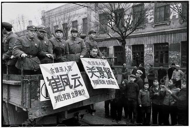 """Following a public trial, seven men and one woman are transported in open trucks from Harbin to Huang Shan Cemetery on the city outskirts for execution. Amid the common criminals and """"counterrevolutionaries"""" are two lovers, Cui Fengyuan (left) and Guan Jingxian (right), who conspired to murder the woman's husband. Harbin, 5 April 1968"""