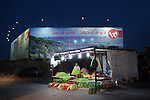 June 2013, Qalandya, Ramallah, West Bank.  Behind the fruit vendor, the biggest advertizing sign in the Palestinian territories displays a giant picture of Haifa, a mixed arab-israli city located in Israel, where many refuges are originated from but denied the access by Israel. The advert, for a telecommunication company, targets the few privileged Palestinian who are allowed to cross the check point and to go to Haifa, offering low tariff to call from Israel into West Bank. Most of Palestinian passing in front the advert could feel bitterness, as they have never seen Haifa, since Israel has established a closure policy in the West Bank. Mahmoud, the fruit vendor, has been to Haifa once in 1998, before the separation wall was built. His sons have never been to Israel.