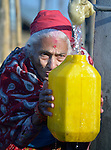 Maya Devi Adhikari, 80, fills a container with water at a community spigot in Makaising, a village in the Gorkha District of Nepal hit hard by a devastating 2015 earthquake.
