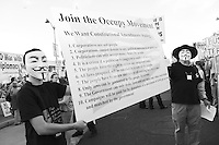 Mesa, Arizona. February 23, 2012 - As Republican candidates debated in the Mesa Arts Center, protesters including undocumented students, tea partiers, occupy movement members and Syrian president opponents, shouted slogans and held up signs and placards outside. In this photograph, two members of the Occupy Movement hold a banner with a message inviting others to join their cause. The Occupy Movement was among several groups who promoted their own social causes. Photo by Eduardo Barraza © 2012