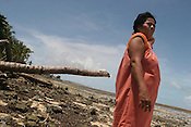Beiataake Orea, a school teacher, stands on the beach at Tenoraereke village, examines an old sea wall and fallen coconut trees destroyed by the sea, expressing her worry about the future of her island of Kiribati in the Pacific Ocean. The islands, and their way of life, are endangered by rising sea water levels which are eroding the fragile atoll, home to approximately 92,000 people.