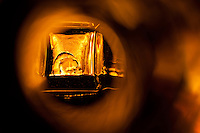 """Beauty at the Bottom: Tequila 10"" - This is a photograph of a tequila bottle, shot right down inside the mouth of the bottle. A fire behind the bottle provides the light source and the color of the image."
