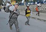 With help from a U.S. soldier, a woman takes home food she received from the World Food Program during a massive distribution in Port-au-Prince, Haiti, less than three weeks after the January 12 earthquake that ravaged the Caribbean nation.