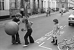 Young children playing safely outside in the street. Gladstone Street, Elephant and Castle,  south London SE1. England. 1975.