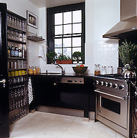 Glasses are displayed on an industrial shelving unit in this black and stainless steel kitchen