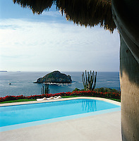 View from under the palapa, or traditional Mexican roof, over the swimming pool to the Pacific Ocean beyond
