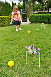 Young girl playing croquet at historic Nunley's Carousel Centennial Celebration on Saturday, June 9, 2012, at Museum Row, Garden City, Long Island, New York, USA. Players used colorful plastic mallets to hit balls through hoops decorated with carousel horses at the 100th Anniversary festivities.