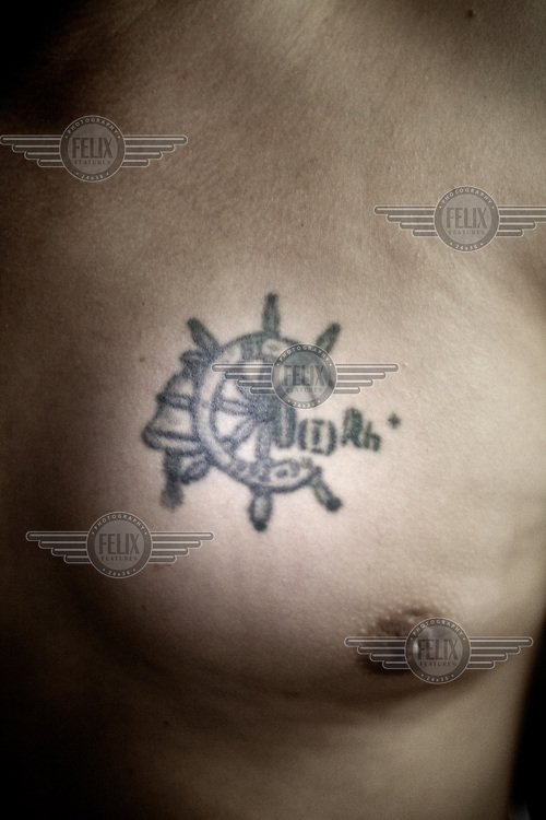 Tattoo on the chest of Maximo, one of the Russian sailors living aboard the Topaz, one of the ships of the former Soviet fleet aground in Puerto de la Luz.After the fall of the Soviet Union in 1991, its enormous fleet of fishing ships and crews were abandoned at different ports around the world; the port of Las Palmas in the Canary Islands had the largest number of ships left there. A sailor who abandons his ship loses the right to demand payment; consequently some crew members have stayed on board for the last 15 years. They have turned the ship into their home; a home that is sinking with its inhabitants in it. Rust eats at the structure and at times the sailors break off parts of the ship to sell them as scrap metal.. They live in an almost invisible limbo.