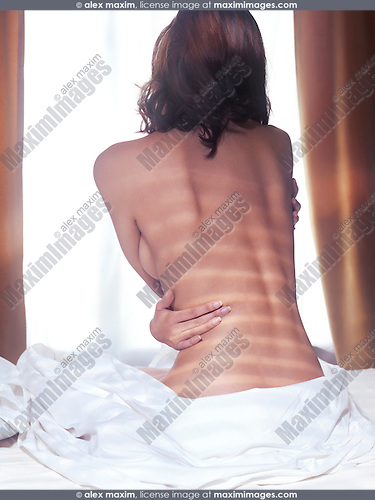 Naked back of a young woman sitting on a bed in front of a window
