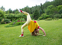 Leisure activity, happy childhood. Girl, child doing somersault in yard. Green, grass and flowerbed. Estonia.
