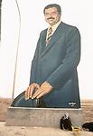 Marsh Arabs. Southern Iraq. Circa 1985. Marsh Arab man at side of road with huge portrait of Saddam Hussein.