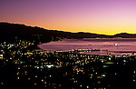 Santa Barbara at sunrise with city lights along the Pacific Ocean beach with Stearns Wharf and Santa Ynez Mountain Range in background, Santa Barbara, California USA