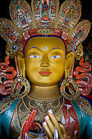 The 12m tall golden sitting statue of Maitreya Buddha as seen on 1st June 2009. Maitreya is the future Buddha said to be preparing to come to earth. The red Chamba Lhakhang of Maitreya is the newest addition to the Thiksay Monastery, Leh town, Ladakh Valley, Jammu & Kashmir state, India. Thiksay, founded in the 15th century, sits on a hill 19 km southeast of Leh town, and houses approximately 100 monks. Photo by Suzanne Lee