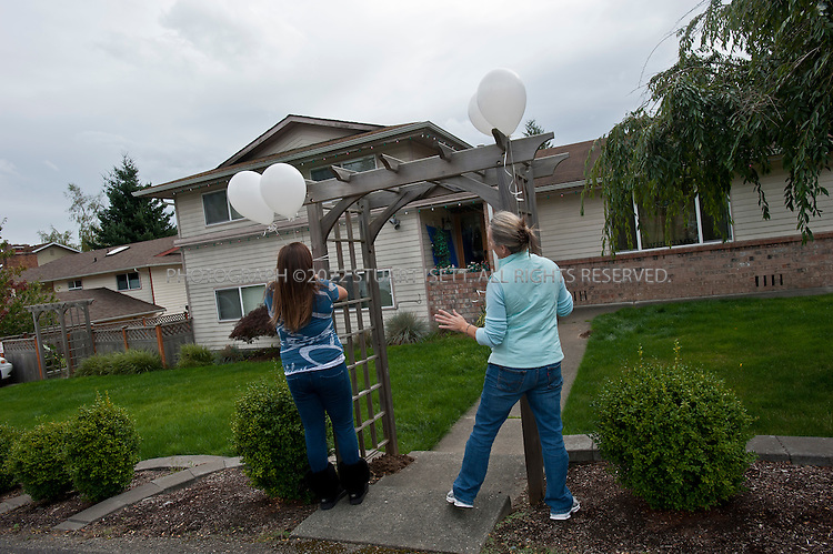 10/4/2011--Seattle, WA, USA..Family friends of Amanda Knox hang balloons at the front gate to her home in West Seattle Oct. 4th 2011. Amanda Knox is expected back in Seattle at 5pm on British AIrways flight after being acquitted of murder in an Italian court on Monday...©2011 Stuart Isett. All rights reserved.