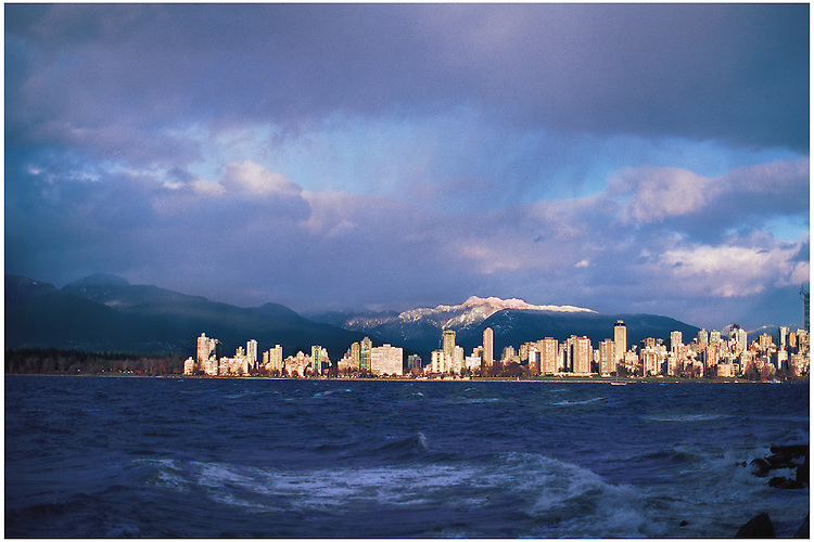 Sunlight striking downtown, the West End peninsula and Stanley Park in Vancouver, and the snow-capped mountains of North Vancouver.