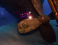 10 June 2014: SCUBA Diver Sally Herschorn discovers the propeller of the USS Kittiwake, a former United States Navy submarine rescue vessel, off Seven Mile Beach, on the West Shore of Grand Cayman Island. Purchased by the government of the Cayman Islands, the Kittiwake was intentionally sunk on January 5, 2011, to create an artificial reef in the Cayman Marine Park. Located in the British West Indies in the Caribbean, the Cayman Islands are renowned for excellent scuba diving, snorkeling, beaches and banking.  Mandatory Credit: Ed Wolfstein Photo *** RAW (NEF) Image File Available ***