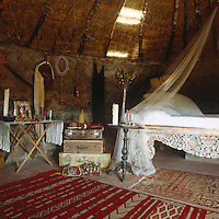 A surprisingly feminine bed beneath a cloud of mosquito netting in an African mud hut that has been furnished with rugs and personal accessories