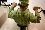 Elderly prisoner exercising on a rowing machine in an indoor recreational room, watched over by guards, in Onomichi prison, Japan.  Monday, May 19th 2008