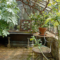 A panel of stained glass rests on a ledge above an old metal roll-top bath at one end of this green house