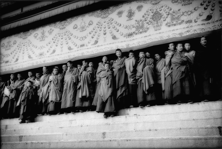 Gelukpa (Yellow Hat) monks atop steps of main prayer hall at Labrang Monastery, Amdo, Tibet.