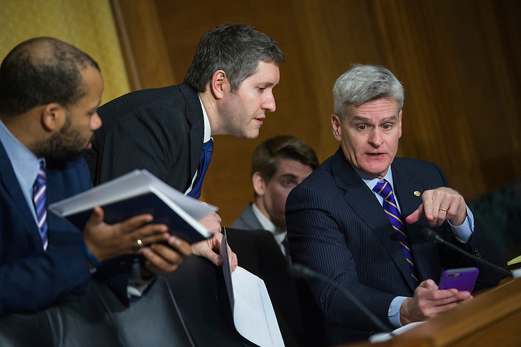 UNITED STATES - JANUARY 31: Sen. Bill Cassidy, R-La., right, speaks with aides during a Senate Finance Committee vote in Dirksen Building that Democrats boycotted on Rep. Tom Price, R-Ga., nominee for HHS secretary, and Steve Mnuchin, nominee for Treasury secretary, January 31, 2017. (Photo By Tom Williams/CQ Roll Call)