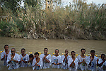 Orthodox-Christian pilgrims of Eritrean and Ethiopian descent, living as migrants in Tel Aviv, Israel, conduct a prayer as they baptise during Epiphany holiday, at the baptismal site of Qasr el-Yahud on the Jordan River, near the West Bank town of Jericho. The site is believed to be where Jesus was baptised by John the Baptist.