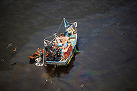 Small fishing boat at the polluted waters with oil spill of Guanabara Bay near Paqueta island.