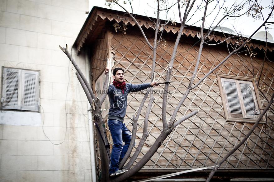 A young man is cutting wood to make fire..A jeun homme coupe du bois pour faire du feu dans la vieille ville d'Alep