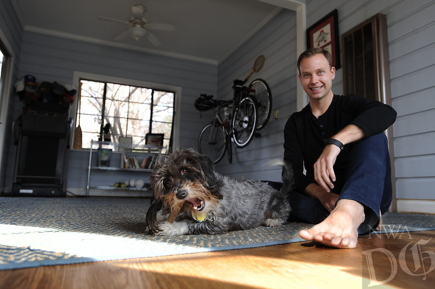 NWA Democrat-Gazette/ANDY SHUPE<br /> Justin Urso, CEO and Founder of Skosay, sits with his dog, Sammy, Friday, Feb. 5, 2016, in his favorite space in his Fayetteville home, a multi-purpose room that he uses to workout and do yoga in.